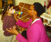Nathalie Bazil, BPHC Health Educator, demonstrates use of a spacer with mask at an asthma home visit in Boston, MA.