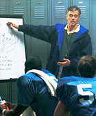 Image of football coach diagramming plays for his team