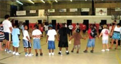 Children in Action Sports Club participants standing in a circle in a gymnasium.