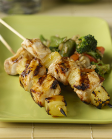 Two Hawaiian huli huli chicken skewers with vegetables on a plate