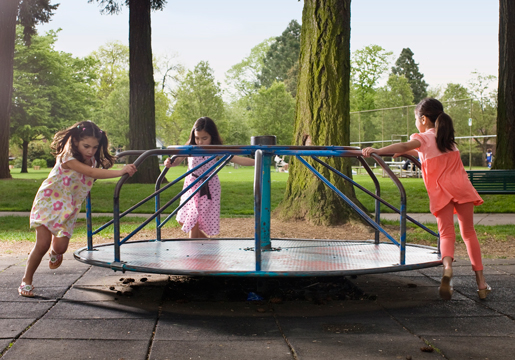 Three girls playing on a merry-go-round