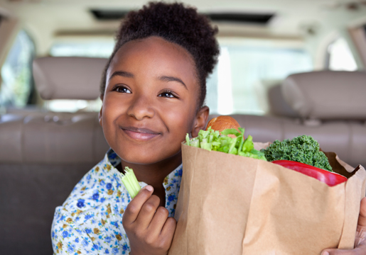 Girl in car eats celery from grocery bag