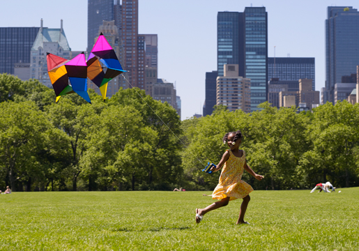 Girl running while flying kite