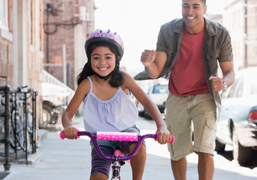 Girl riding bike with father cheering