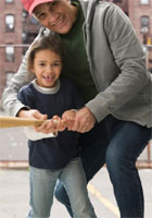 A grandfather helps his granddaughter swing a baseball bat.