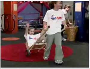 Screenshot of video showing a child pulling another child on a handcart