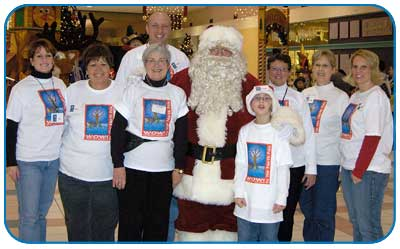 Seven adults and one child in matching t-shirts stand with Santa Claus at the mall