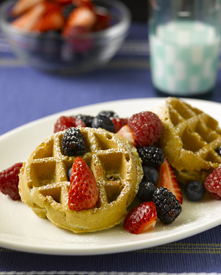 Oatmeal pecan waffles with fruit topping on a plate