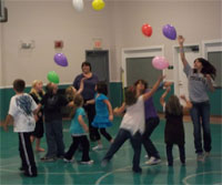 Students participating in the CATCH Kids Club at Moscow Elementary School play balloon games in their gymnasium.