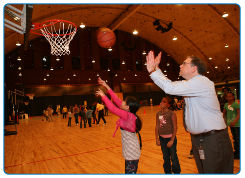 Dr. Tabak teaching a young girl to play basketball