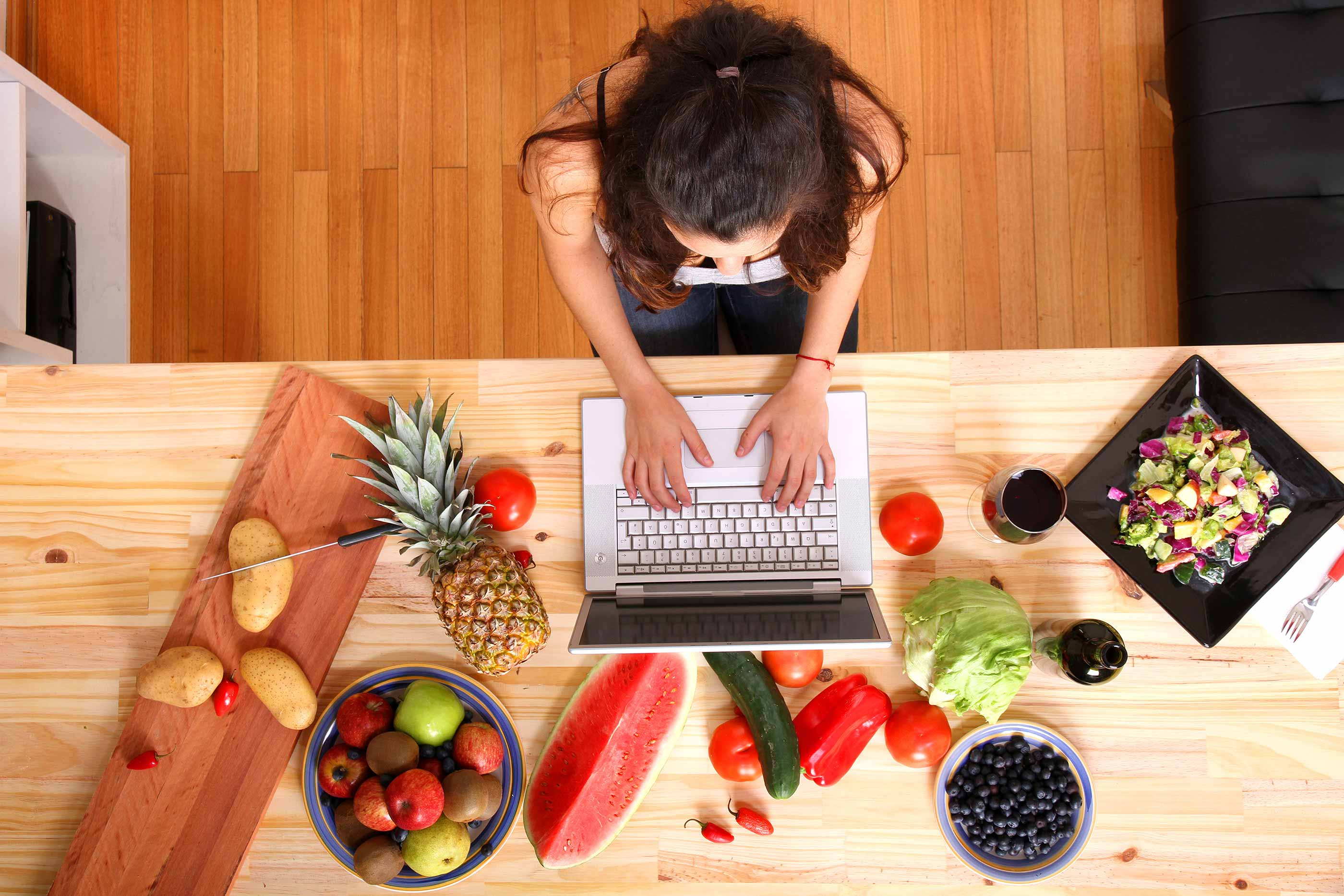 Woman researching recipes on a laptop, on a table surrounded by fresh produce.