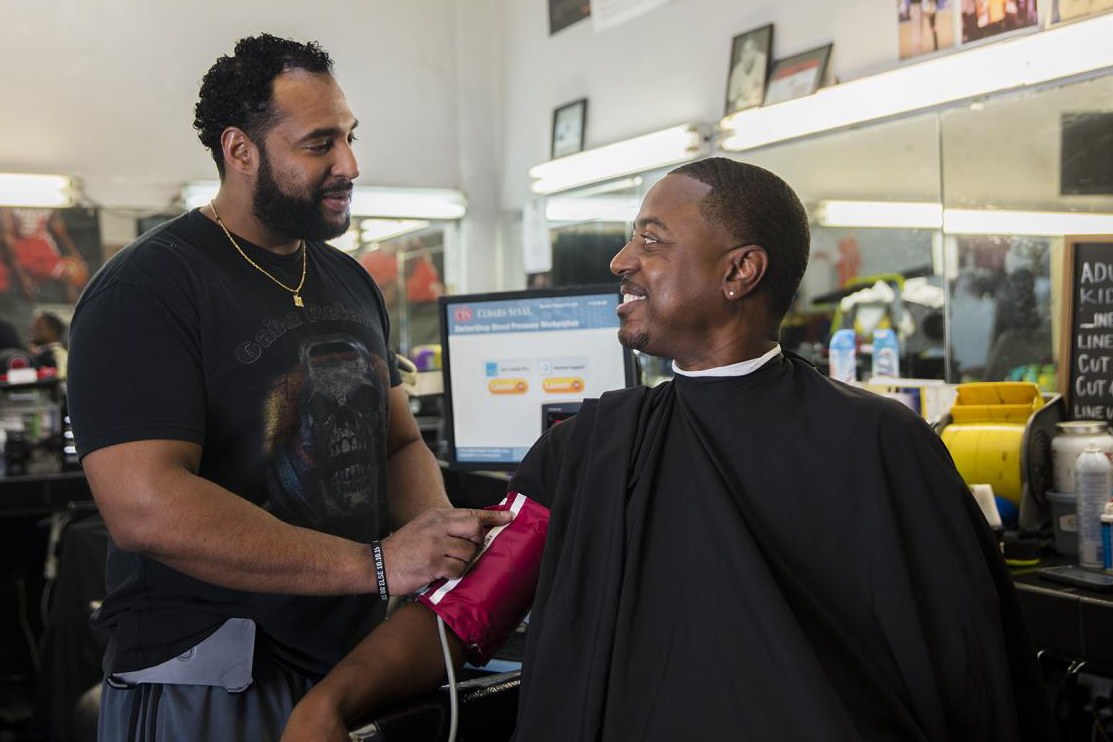 Eric Muhammad (left), owner of A New You Barbershop in Inglewood, Calif., prepares to measure the blood pressure of long-time customer Marc Sims. Photo credit: Smidt Heart Institute at Cedars-Sinai Medical Center.