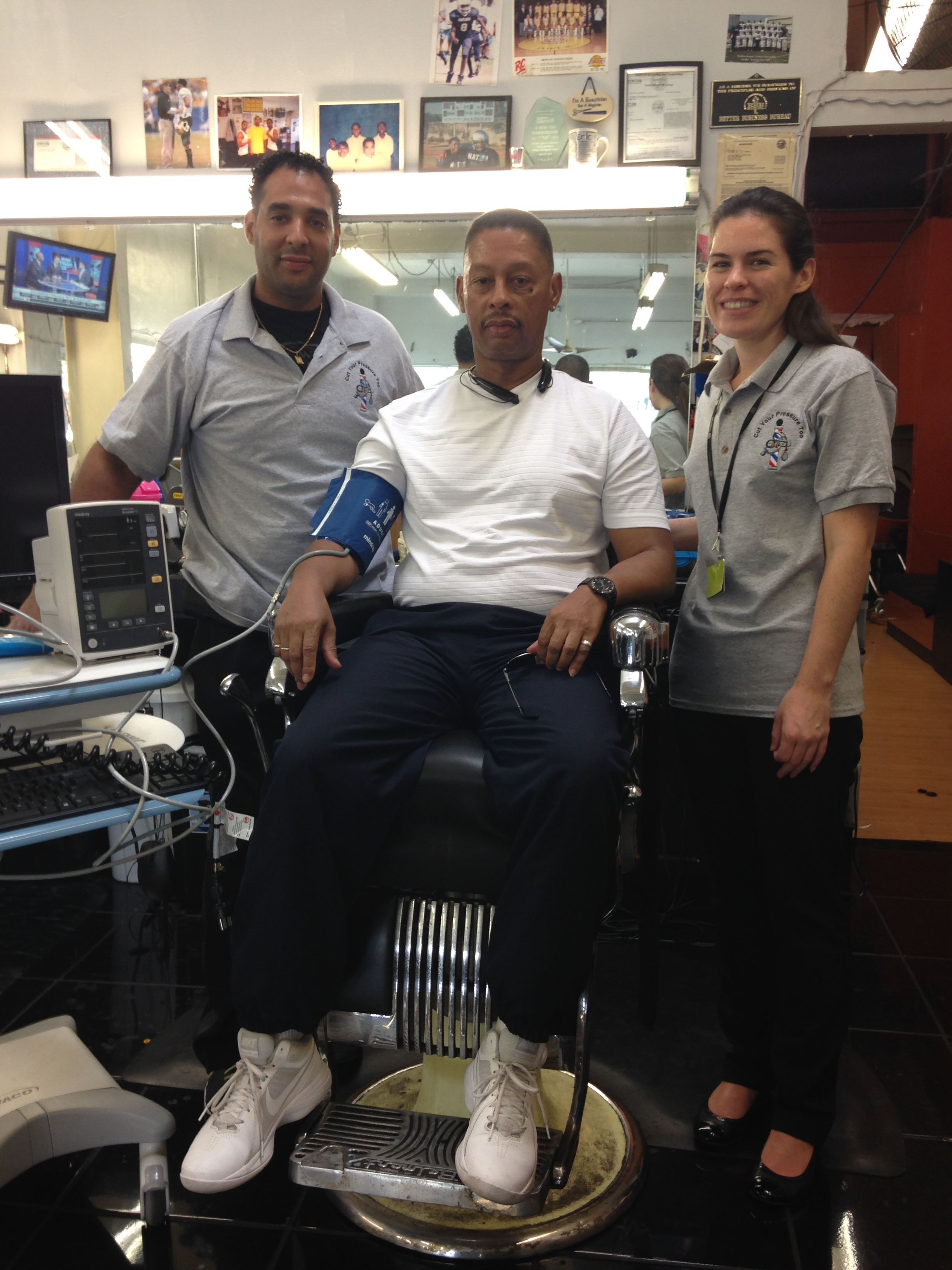 "Eric Muhammad (left) stands next to barbershop customer (seated) and a visiting pharmacist (right). The logo on the gray polo shirts shows a blood pressure cuff wrapped around a barber pole with the caption ""Cut Your Pressure Too."""
