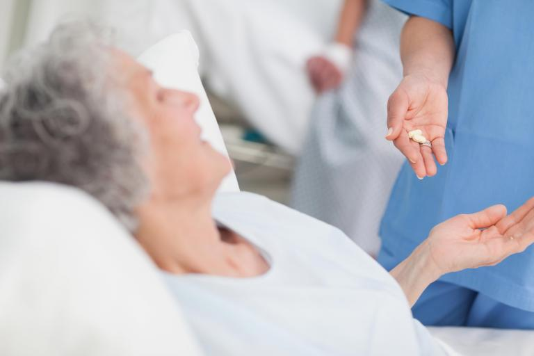 Senior patient with open hand taking medicine from a health provider.