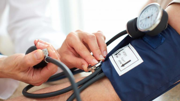 Patient having blood pressure taken by medical professional.
