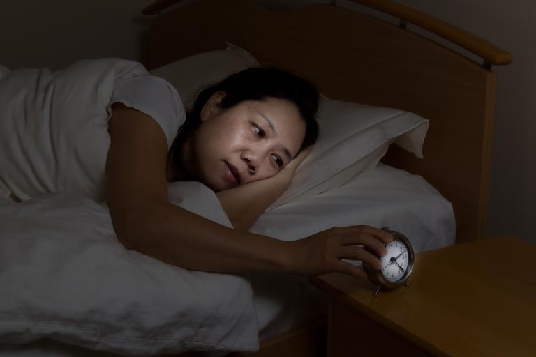 Middle age woman having trouble sleeping, with old school alarm clock at side of bed.