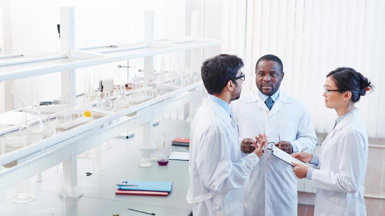 Three lab members in white coats engaged in conversation