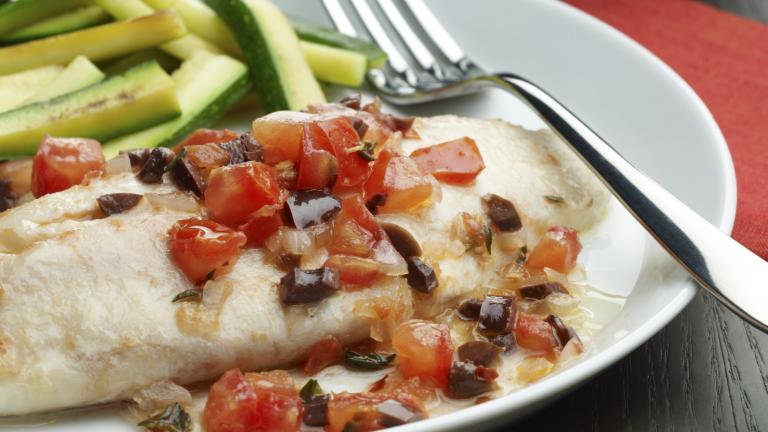 Image of a plate with baked tilapia and tomatoes.
