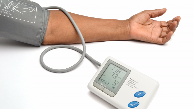 Stock image of blood pressure measuring machine attached to a person's arm