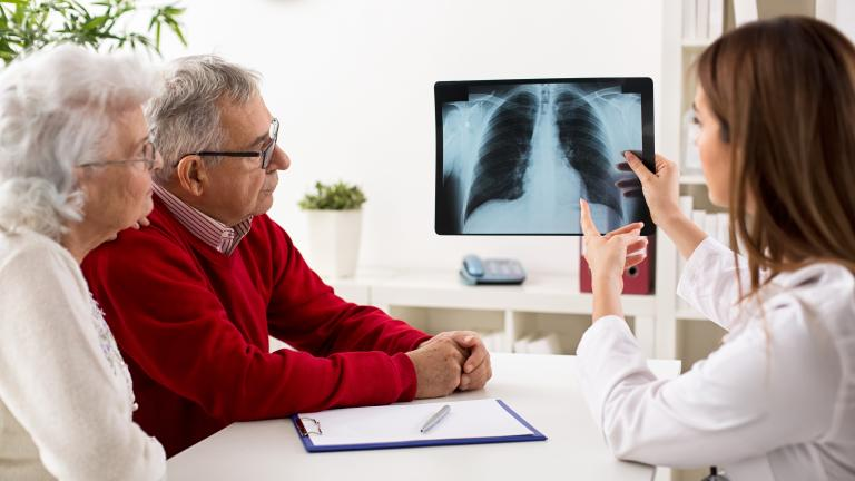 Doctor shows results to senior patients x-ray of the lungs