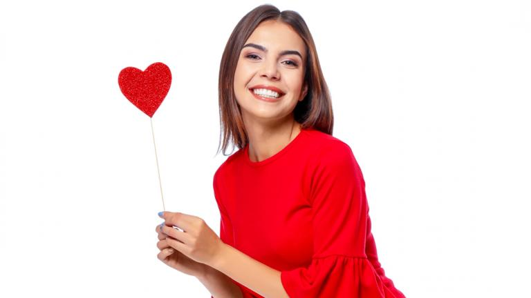 Woman wearing red dress, holding a red paper heart