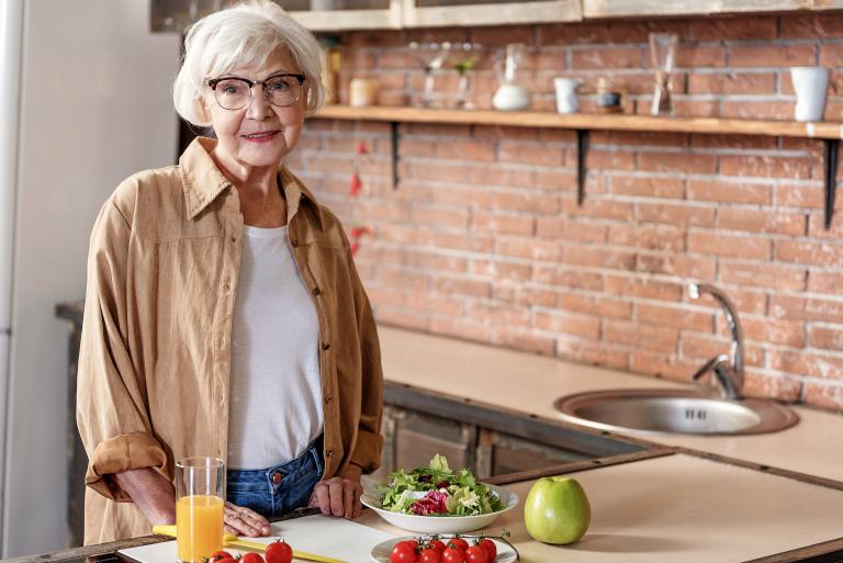 Elderly woman standing up at the kitchen counter, with a glass of orange juice, vegetables and an apple.