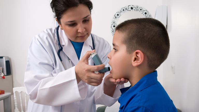 Medical professional showing a kid how to use an inhaler. Stock Photo.