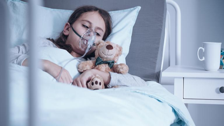 Kid with cystic fibrosis lying in a hospital bed with oxygen mask and plush toy - Image