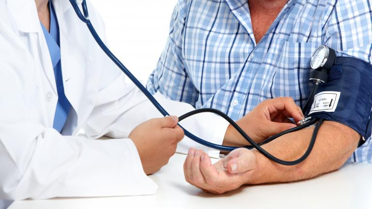 Medical professional taking man's blood pressure