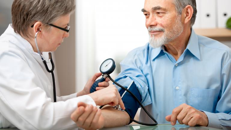 Medical professional taking blood pressure readings of middle age man