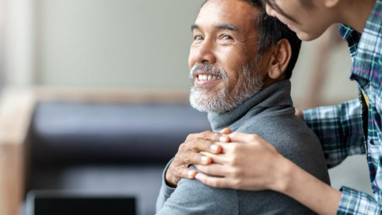 Older asian man smiling, being hugged by younger person