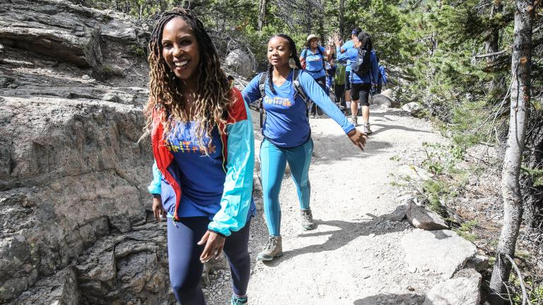 A black woman walking up mountain trail with other women behind her.
