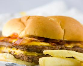 Copyrighted photo of a greasy bacon cheeseburger with french fries.