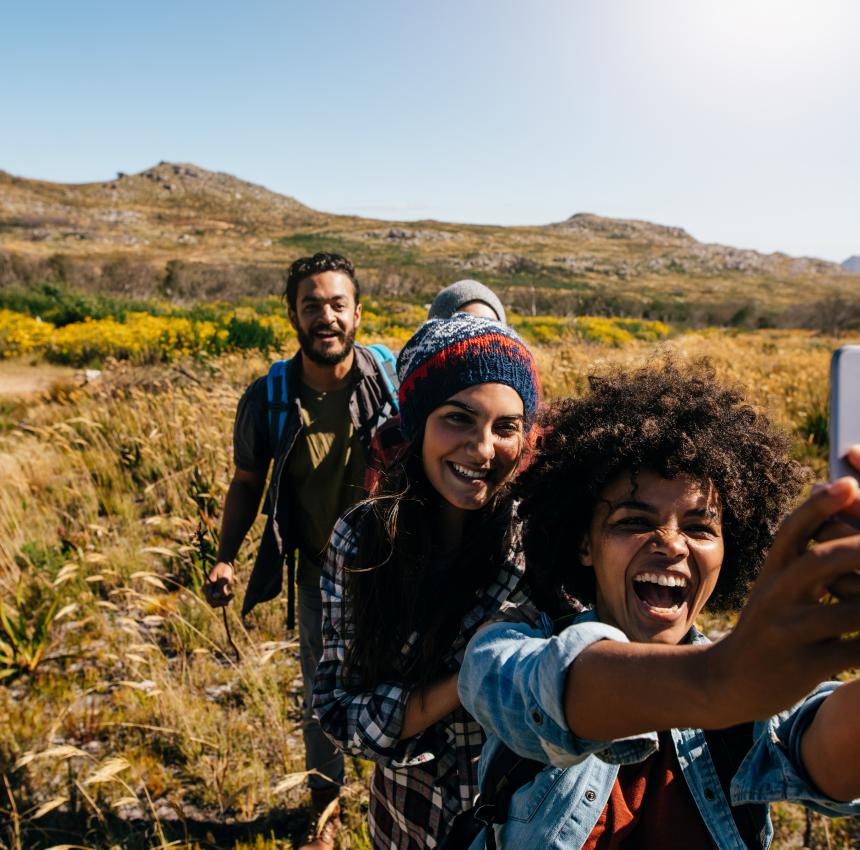 Two women standing in front of a man looking at phone to take a selfie on a hiking trail