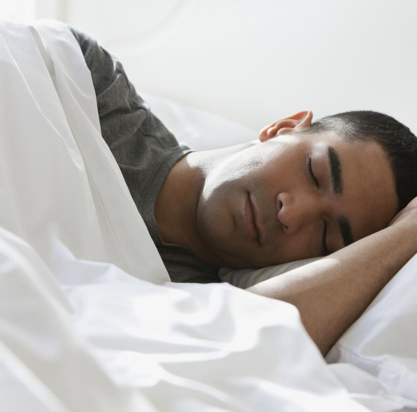 Man sleeping peacefully on his side, surrounded by white sheets